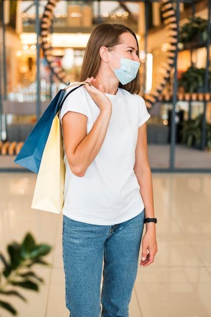 Ritratto di giovane donna alla moda che indossa la maschera per il viso Foto Gratuite