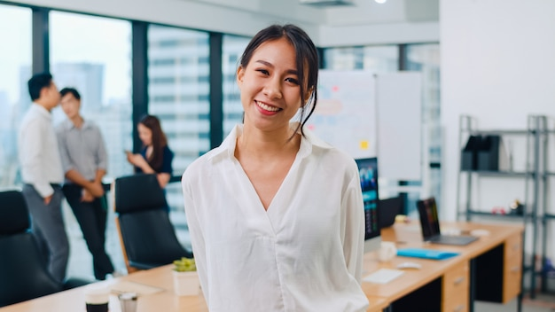 Portrait of successful beautiful executive businesswoman smart casual wear looking at camera and smiling in modern office workplace. young asia lady standing in contemporary meeting room. Free Photo