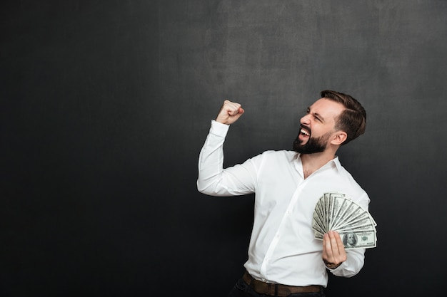 Portrait of successful guy in white shirt rejoicing like winner with fan of 100 dollar bills in hand, clenching fist aside over dark gray Free Photo