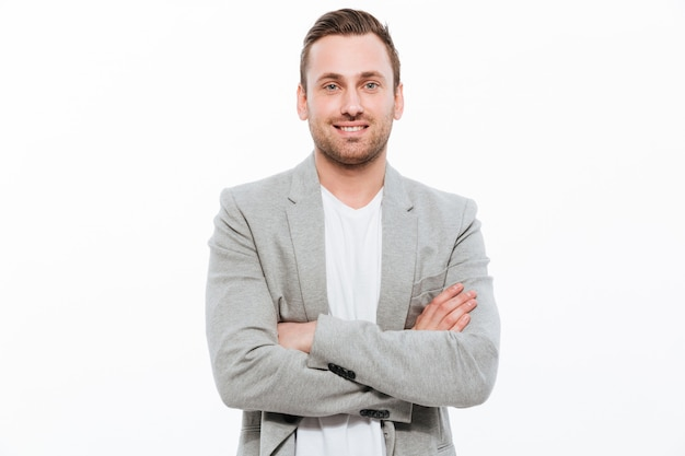 Portrait of successful man having stubble posing with broad smile keeping arms folded Free Photo
