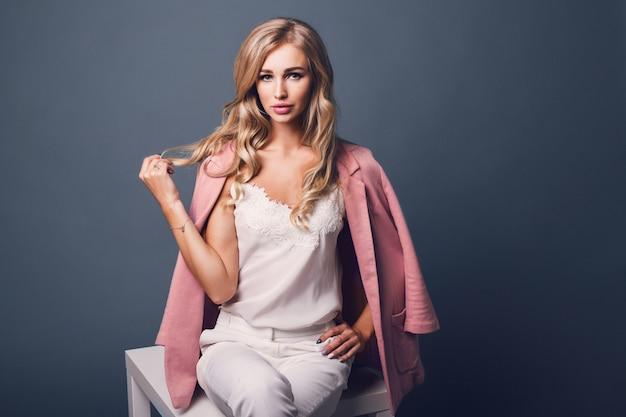 Ritratto di successo giovane donna bionda seducente in giacca pastello rosa che si siede sul tavolo Foto Gratuite