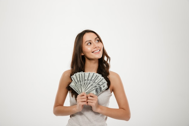 Portrait of successful young woman with long hair holding lots of money cash, smiling on camera over white wall Free Photo