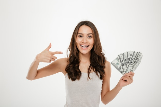 Portrait of successful young woman with long hair showing lots of money cash, smiling on camera over white wall Free Photo