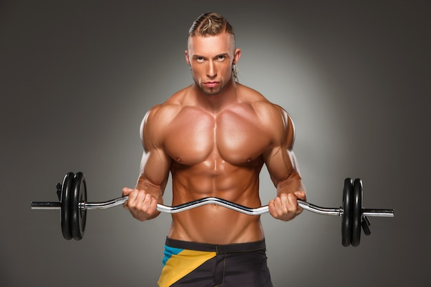Portrait of super fit muscular young man working out in gym. Free Photo