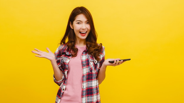 Portrait of surprised asian female using mobile phone with positive expression, dressed in casual clothing and looking at camera over yellow wall. happy adorable glad woman rejoices success. Free Photo