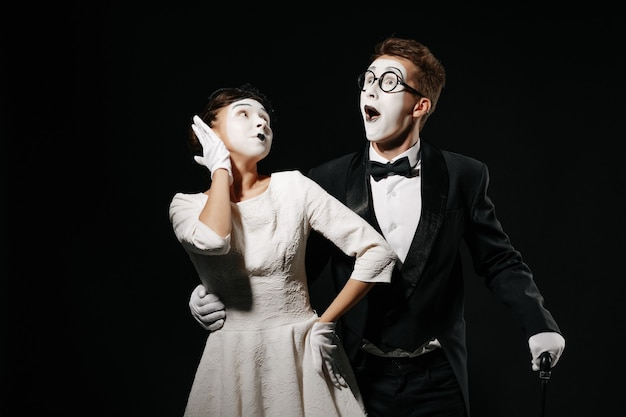 Portrait of surprised couple mime on black background. man in tuxedo and glasses and woman in white dress Premium Photo