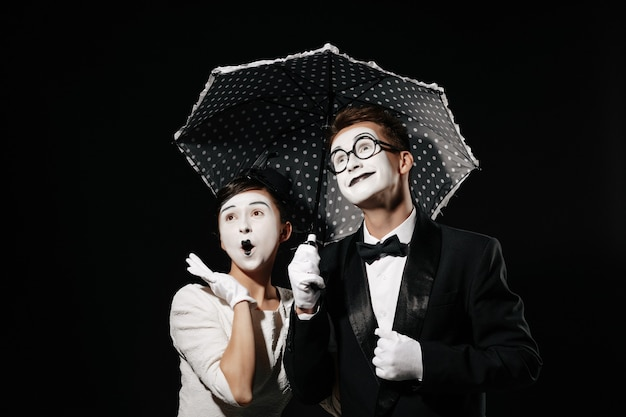 Portrait of surprised couple mime with umbrella on black background. man in tuxedo and glasses and woman in white dress Premium Photo