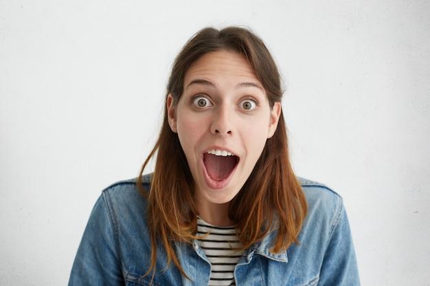 Ritratto di donna sorpresa con occhi infastiditi e bocca ampiamente aperta che si sente scioccata mentre viene espulsa dall'università. Foto Gratuite