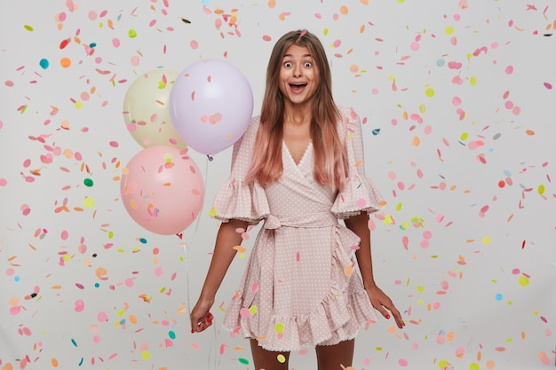 Portrait of surprised pretty young woman with long dyed pastel pink hair and opened mouth celebrating birthday, holding colorful baloons in hand Free Photo