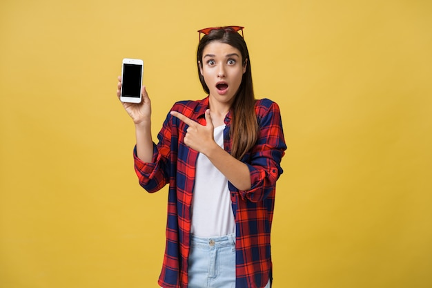 Portrait of a surprised woman in casual cloth showing blank screen mobile phone Premium Photo