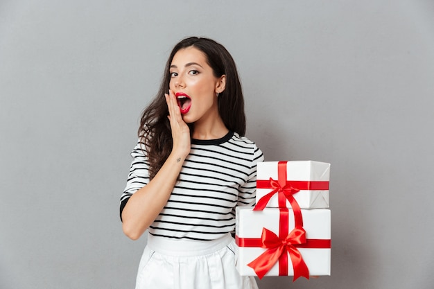 Portrait of a surprised woman holding stack of gift boxes Free Photo