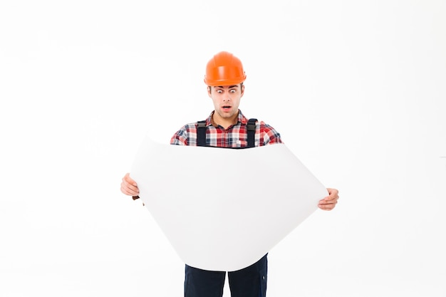 Portrait of a surprised young male builder examining paper draft Free Photo