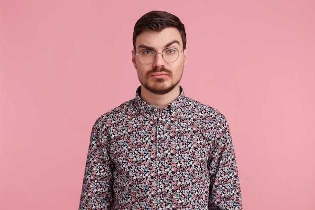 Ritratto di sospettoso pensieroso giovane maschio barbuto con gli occhiali in maglietta colorata pensando a qualcosa, un sopracciglio sollevato interrogatorio, con espressione seria e perplessa Foto Gratuite