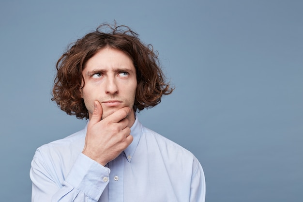 Portrait of suspicious pensive young male in casual shirt touching face while thinking over something Free Photo