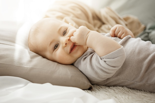 Portrait of sweet smiling newborn daughter lying on cozy bed. child looks at camera and touching face with her little hands. childhood moments. Free Photo
