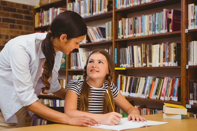 Portrait of teacher assisting little girl with homework in the library Premium Photo