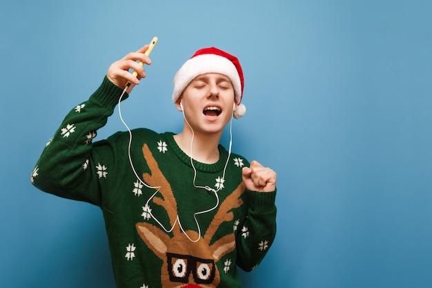 音楽を聞いているクリスマスセーターと肖像画のティーンエイジャーの少年 Premium写真