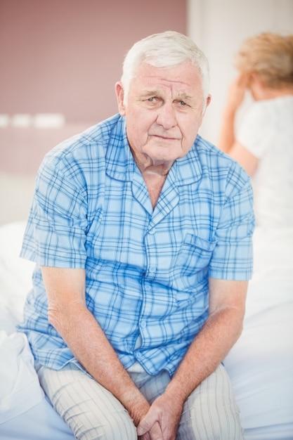 Portrait of tensed senior man sitting on bed Premium Photo