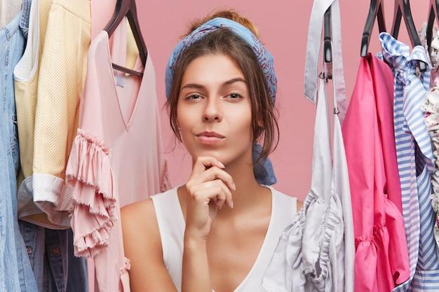 Ritratto di donna pensosa con sciarpa sulla testa, in piedi vicino a grucce con vestiti, pensando a cosa comprare. shopaholic femminile in boutique con espressione pensierosa, avendo una scelta difficile Foto Gratuite