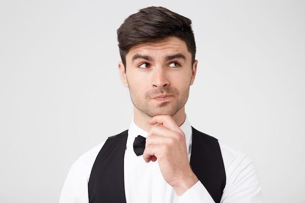 Ritratto di giovane premuroso che tiene la mano sul mento e distoglie lo sguardo in piedi isolato sopra il muro bianco Foto Gratuite