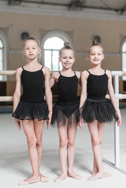 Portrait of three ballerina girls standing in dance studio Free Photo