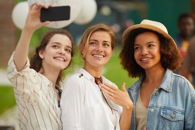 Portrait of three beautiful young women taking selfie photo via smartphone during outdoor party in summer Premium Photo