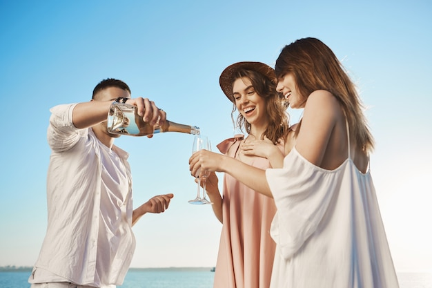 Portrait of three young attractive people who are on vacation traveling by yacht and drinking champaign, enjoying fresh sea air. friend invited two ladies to his boat, celebrating start of summer. Free Photo