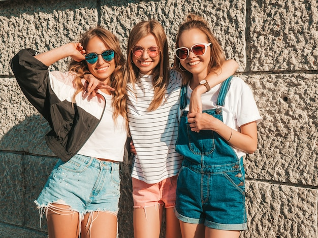 Portrait of three young beautiful smiling hipster girls in trendy summer clothes. sexy carefree women posing in the street near wall.positive models having fun in sunglasses.hugging Free Photo