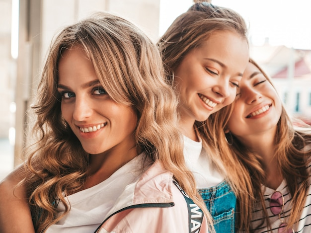 Portrait of three young beautiful smiling hipster girls in trendy summer clothes. sexy carefree women posing on the street.positive models having fun.hugging Free Photo