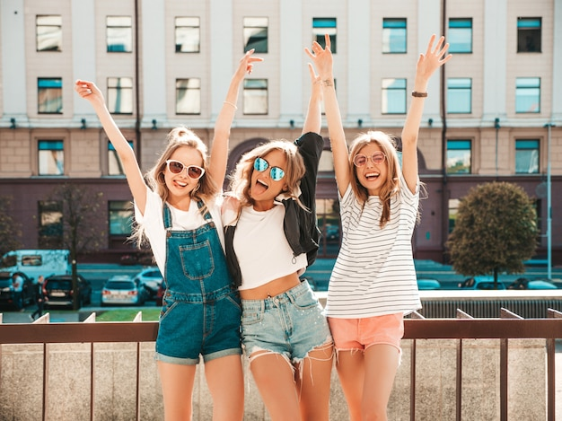 Portrait of three young beautiful smiling hipster girls in trendy summer clothes. sexy carefree women posing on the street.positive models having fun in sunglasses.raising hands Free Photo