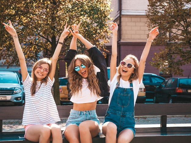 Portrait of three young beautiful smiling hipster girls in trendy summer clothes.sexy carefree women sitting on the bench in the street.positive models having fun in sunglasses.raising hands Free Photo