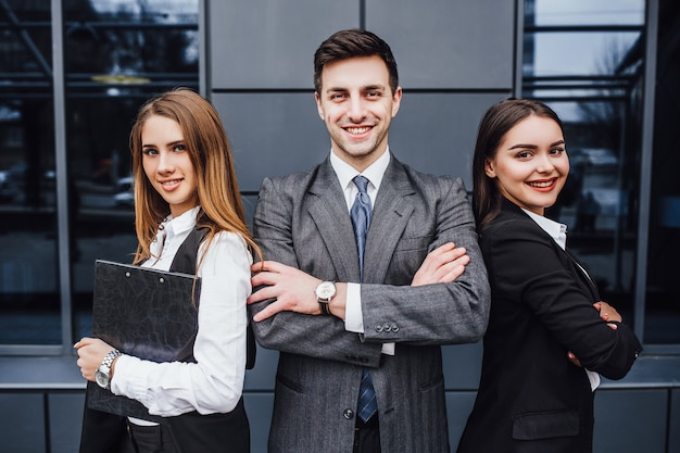 Portrait of three young smiling lawyers standing crossed arms. Premium Photo