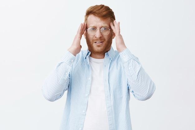 Ritratto di imprenditore maschio stanco di bell'aspetto con i capelli rossi e la barba in bicchieri, tenendo le mani sulle tempie e fissando sfocato, avendo mal di testa Foto Gratuite