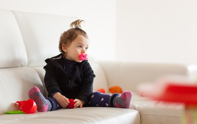 Portrait toddler baby girl playing on the sofa. Premium Photo