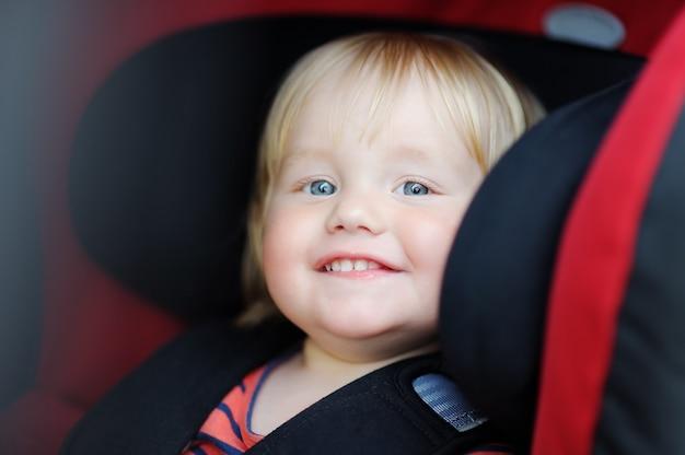 Portrait of toddler boy sitting in car seat Premium Photo
