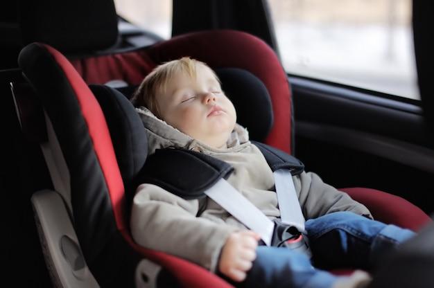 Portrait of toddler boy sleeping in car seat Premium Photo