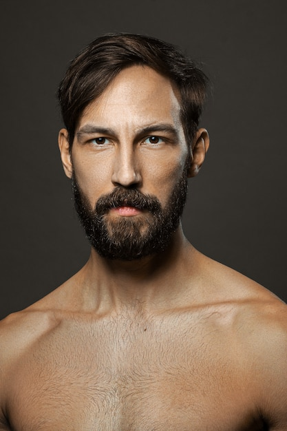 Portrait of topless serious man with beard and mustache looking straight severe. Premium Photo
