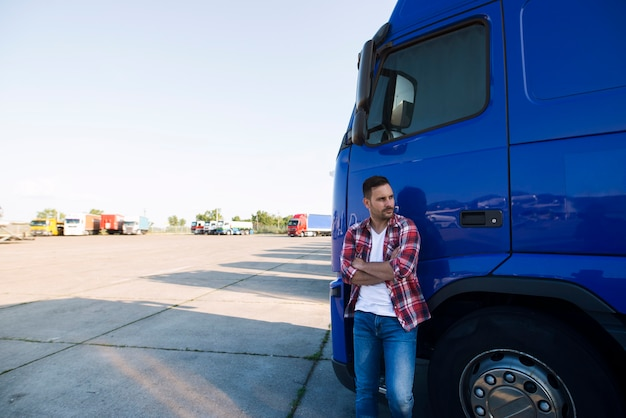 Portrait of trucker in casual clothes standing by his truck vehicle and looking sideways Free Photo