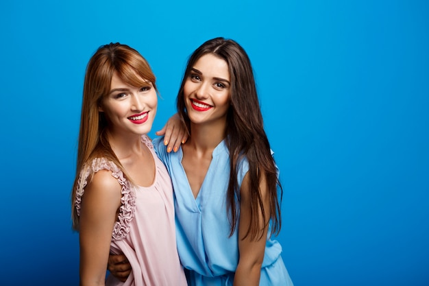Portrait of two beautiful girls over blue wall Free Photo