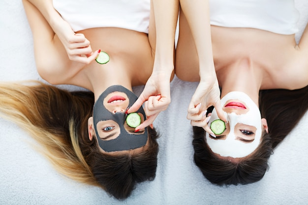 Portrait of two beautiful girls with facial cream on their faces and smiling Premium Photo