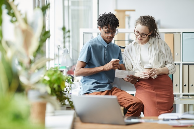 Portrait of two creative young people looking at printed photographs during coffee break in modern office, copy space Premium Photo