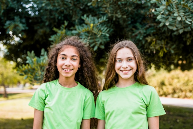 Portrait of two cute girls wearing green t-shirt standing in park Free Photo