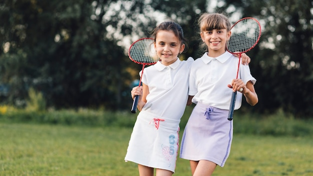 Portrait of two female friends standing with badminton in the park Free Photo