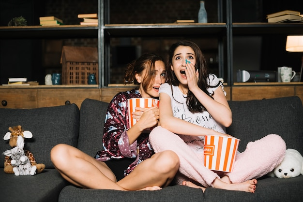 Portrait of two frightened female friends watching television Free Photo