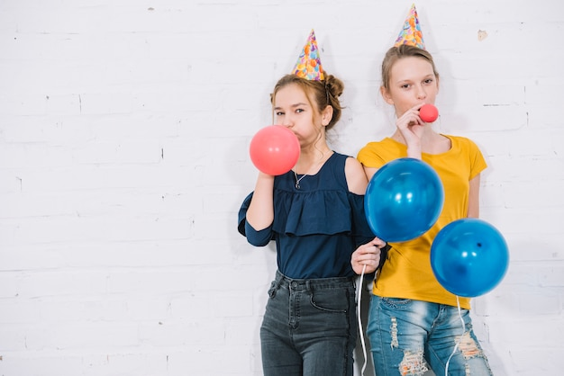 Portrait of two girls blowing red balloons standing against the white wall Free Photo