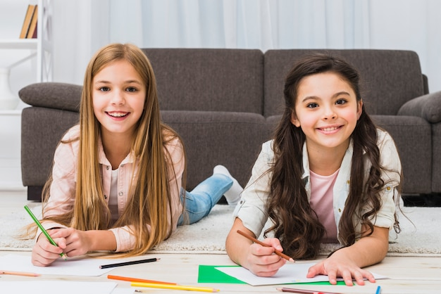 Portrait of two girls laying on carpet drawing color with pencil looking to camera Free Photo