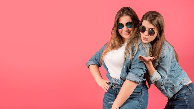 Portrait of two girls on red background Free Photo