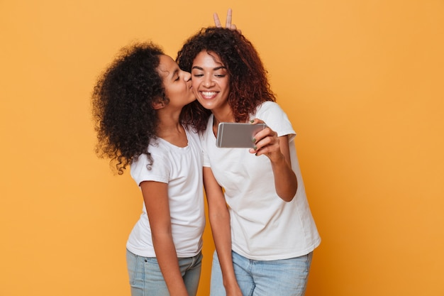 Portrait of a two happy afro american sisters taking selfie with smartphone, cute kiss Free Photo