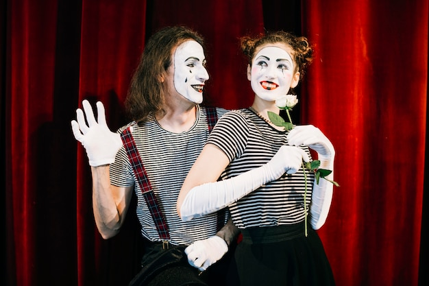 Portrait of two happy mime artist in front of red curtain Free Photo