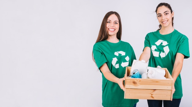 Portrait of two happy women holding wooden box full of bottles and tin cans Free Photo